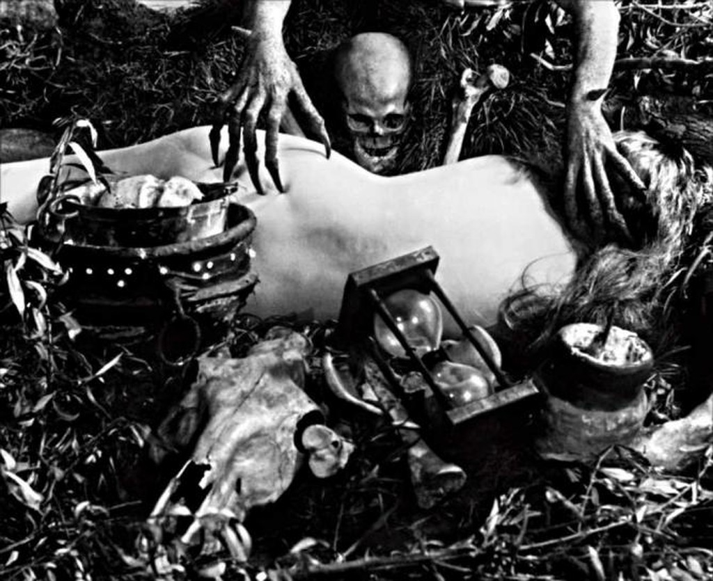 A nude woman lays on the grass amongst an array of items, with her back turned. Long skeletal hands reach for her.