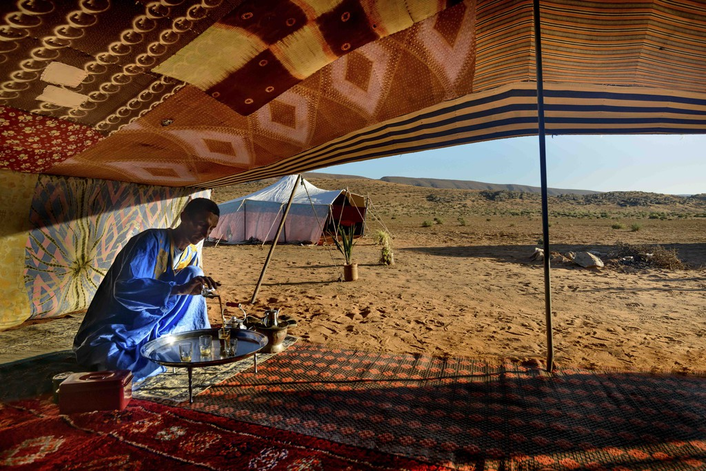 Berber man preparing tea for guests at a camp near Guelmim in the Sahara desert, Morocco.