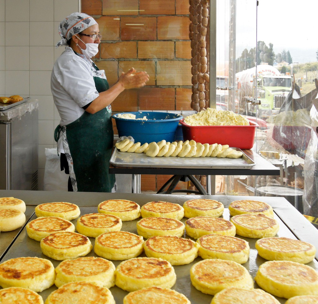 Woman in window of highway truck stop making arepas (corn bread), Bogota, Colombia