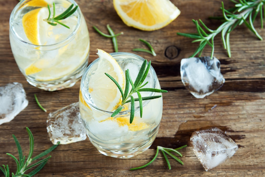 Cocktail with lemon, rosemary and ice on wooden table