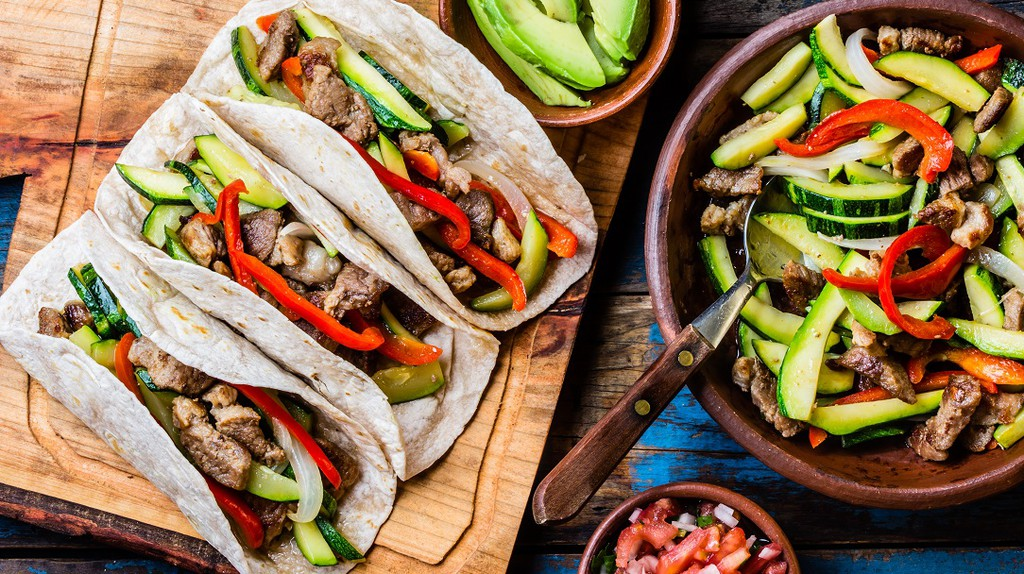 Mexican pork tacos with vegetables and salsa © Larisa Blinova / Shutterstock