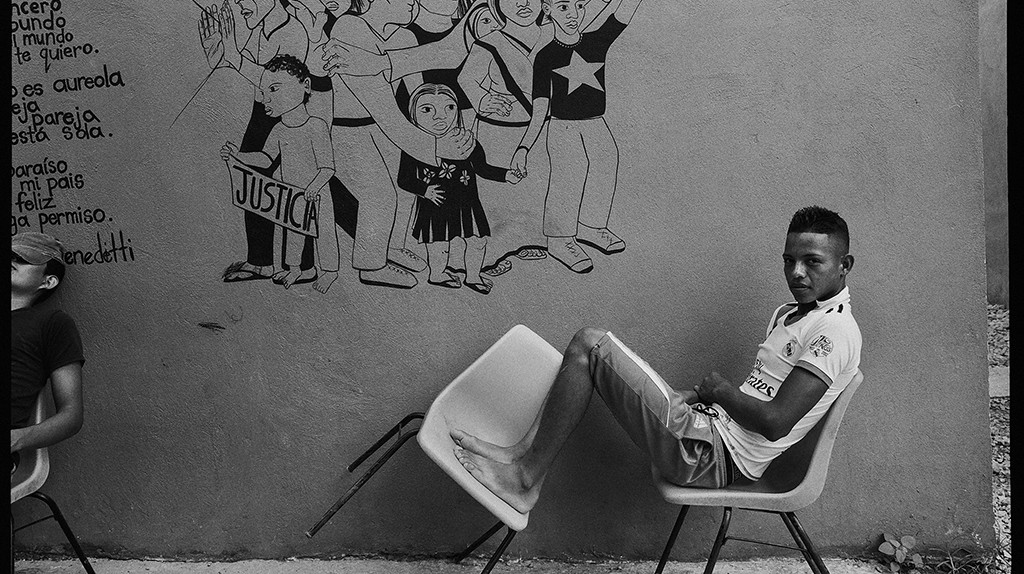 Tenosique, Mexico. A resident of La 72 shelter waits for mealtime in front of one of the many murals painted by volunteers and residents.  The painting of a group of marchers demanding justice and freedom sits alongside a poem by Mario Bendetti, a Uruguayan writer forced to flee his country after a military coup in 1973. |© Graciela Iturbide, 2015