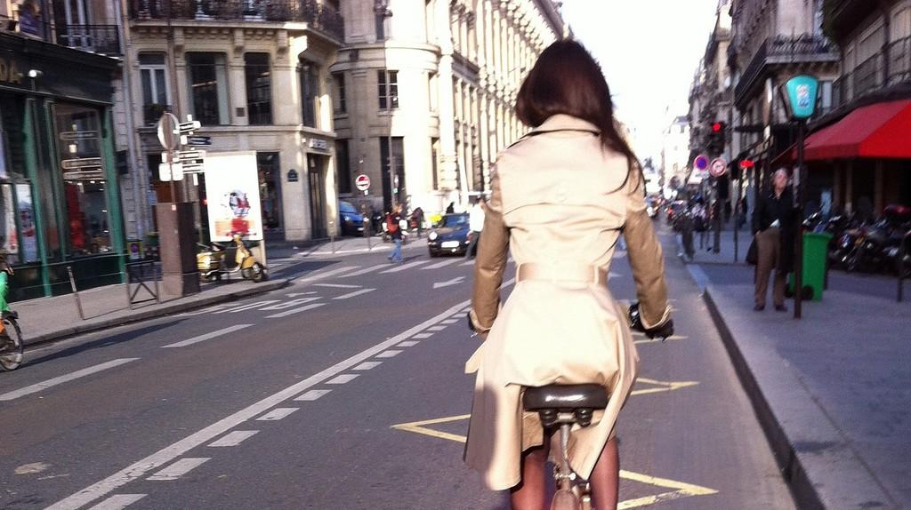 Stylish woman riding a bicycle down a Paris street │© ParisSharing