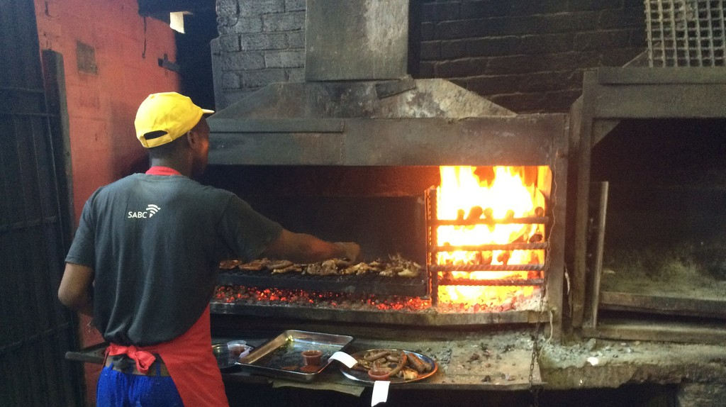 A staff member at Mzoli's Place braais meat for patrons in Gugulethu township © Jonathan Khoo/Flickr