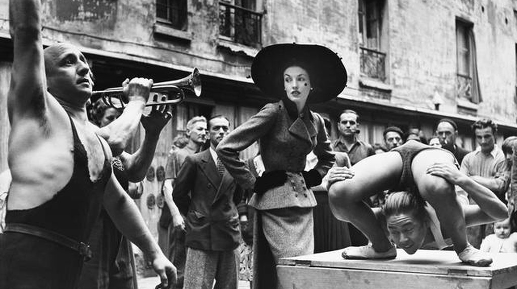 Elise Daniels with street performers, suit by Balenciaga, Le Marais, Paris, August 1948. Photograph by Richard Avedon. © The Richard Avedon Foundation