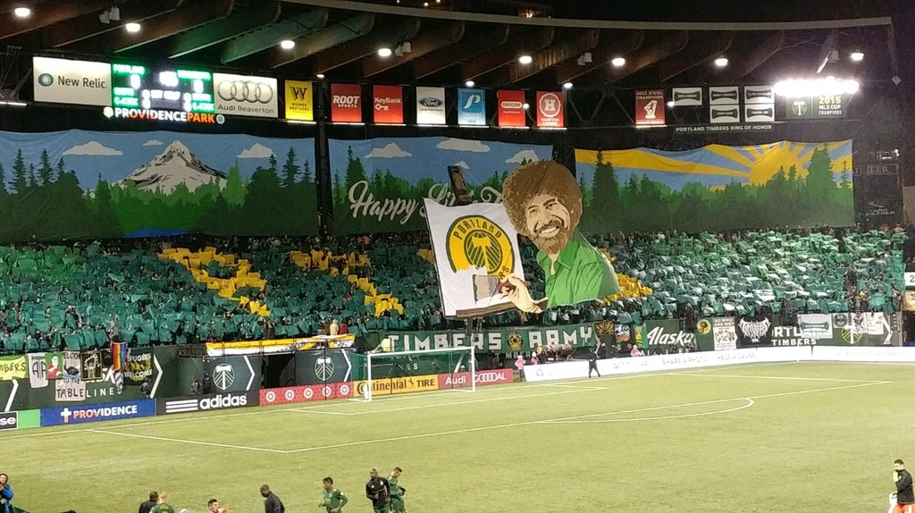 The Timbers Army holds up a Bob Ross-inspired tifo ahead of the team's 2017 opener | © Michael LoRé