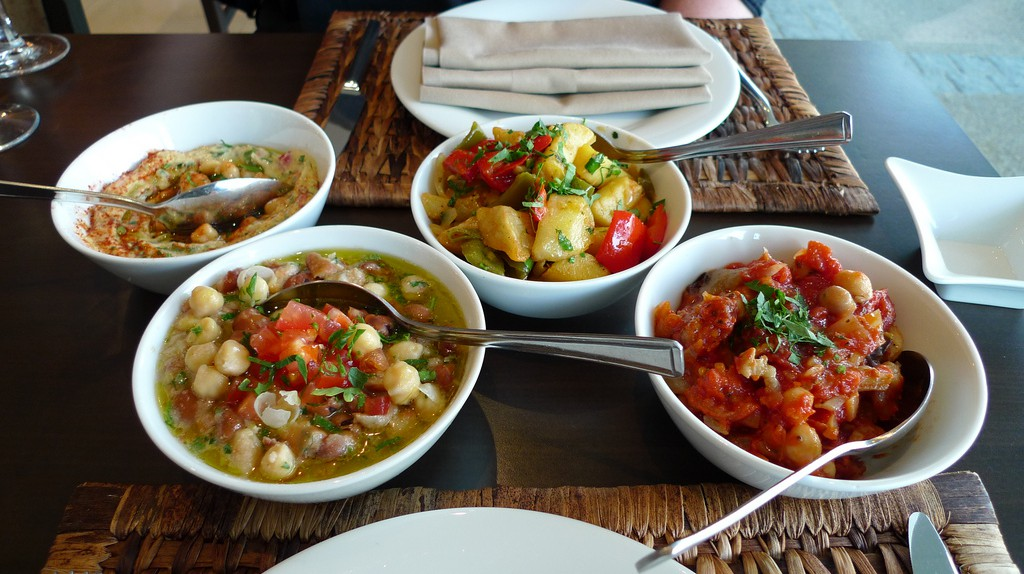 """<a href=""""https://www.flickr.com/photos/55935853@N00/3639283205/"""" target=""""_blank"""" rel=""""noopener noreferrer"""">A selection of different Lebanese mezza dishes, L-R: hommos, foul moudamas, batata harra, and moussaka   © Ewan Munro / Flickr</a>"""