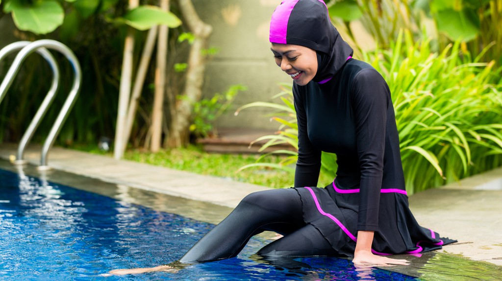 Woman wearing a burkini relaxing by the swimming pool/Shutterstock Images