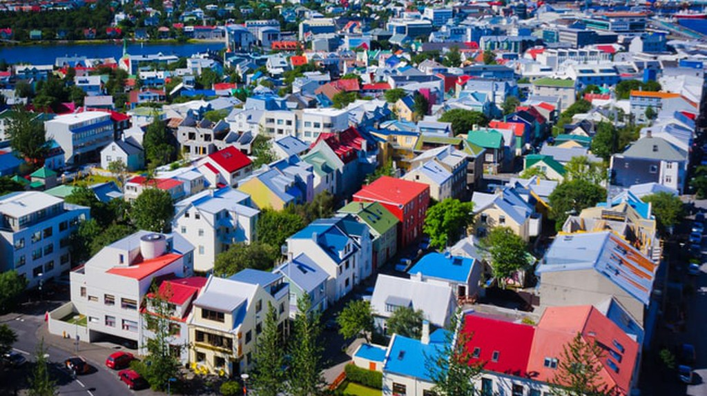 Beautiful super wide-angle aerial view of Reykjavik with harbor and skyline mountains and scenery beyond the city, seen from the observation tower of Hallgrimskirja |© Tsuguliev / Shutterstock