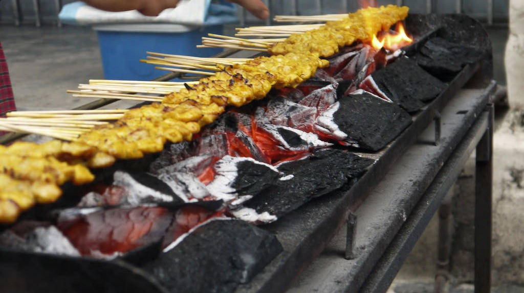 Satay being cooked over charcoal grill © Khairil Zhafri/Flickr