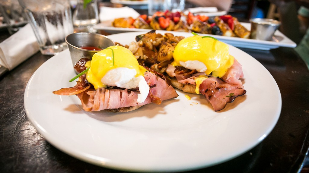 Blu Jam Benedict - Poached eggs on a toasted English muffin with Black Forest Ham, crispy bacon, topped with hollandaise sauce, served with potatoes Ι © City Foodsters/Flickr