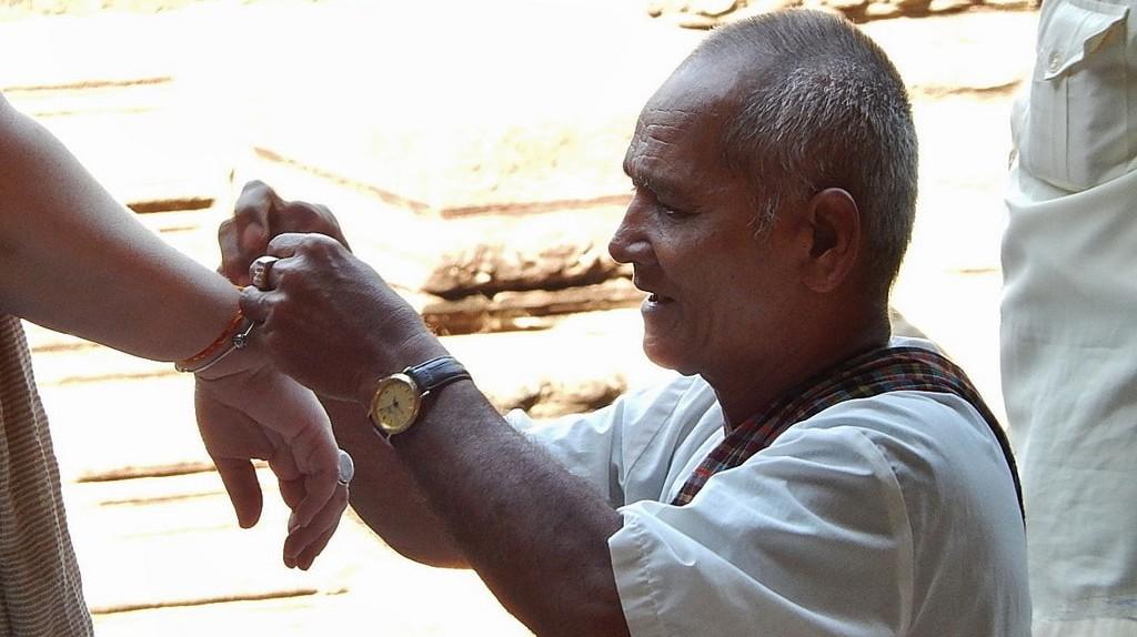 Monk ties thread around a tourist's wrist | © Michael Coghlan / Shutterstock