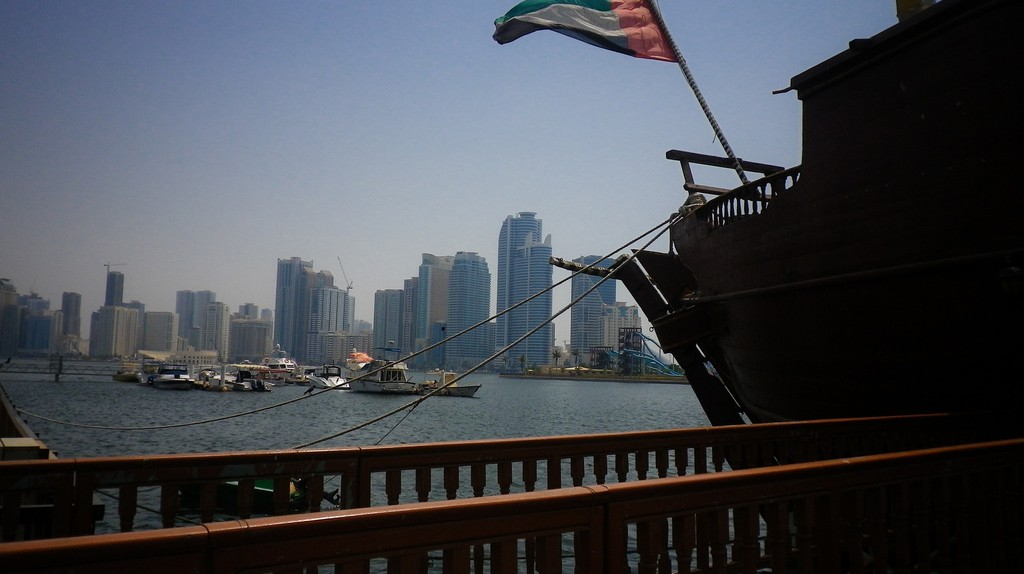 The UAE flag flying off of a traditional dhow boat