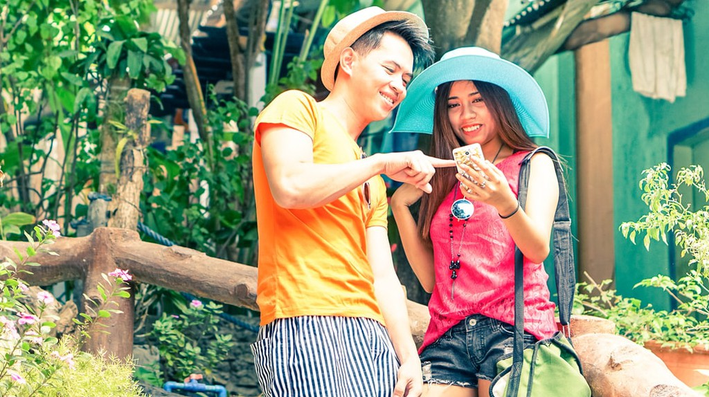 Happy couple of tourists using mobile
