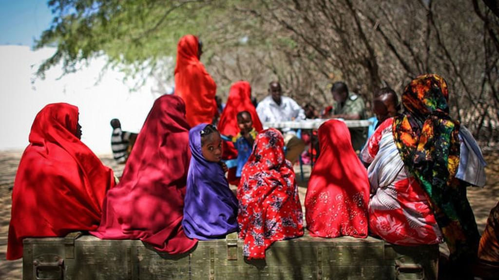 Women and girls from Burundi sitting in the shade