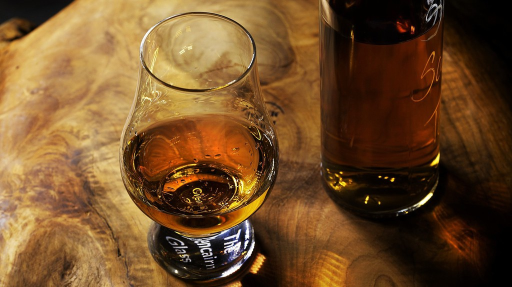 Glass of whiskey on a wooden table.