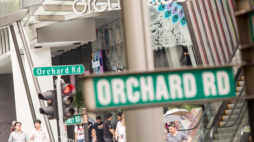 Pedestrians and shoppers cross Orchard Road in Singapore