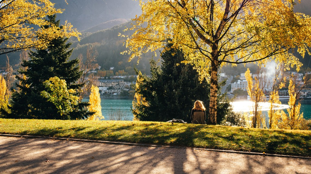 A person relaxes at Queenstown Gardens