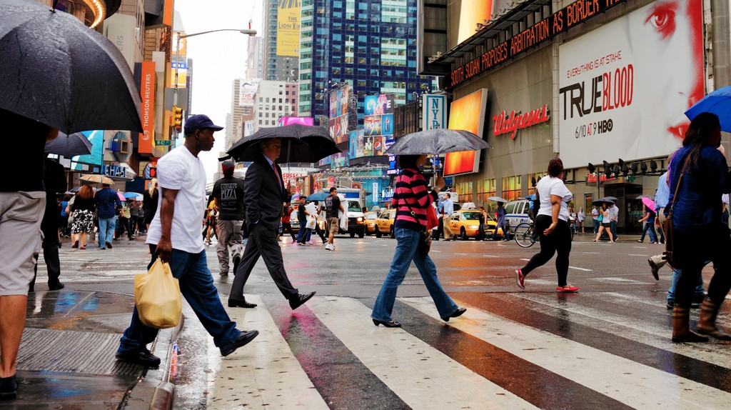 People crossing a street at rainy Times Square