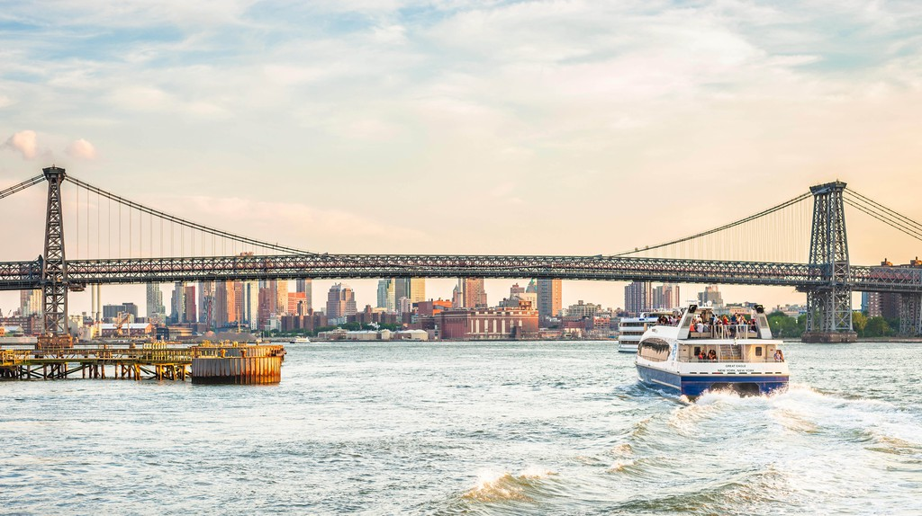 The ferry sails on the East River, New York, Williamsburg bridge.