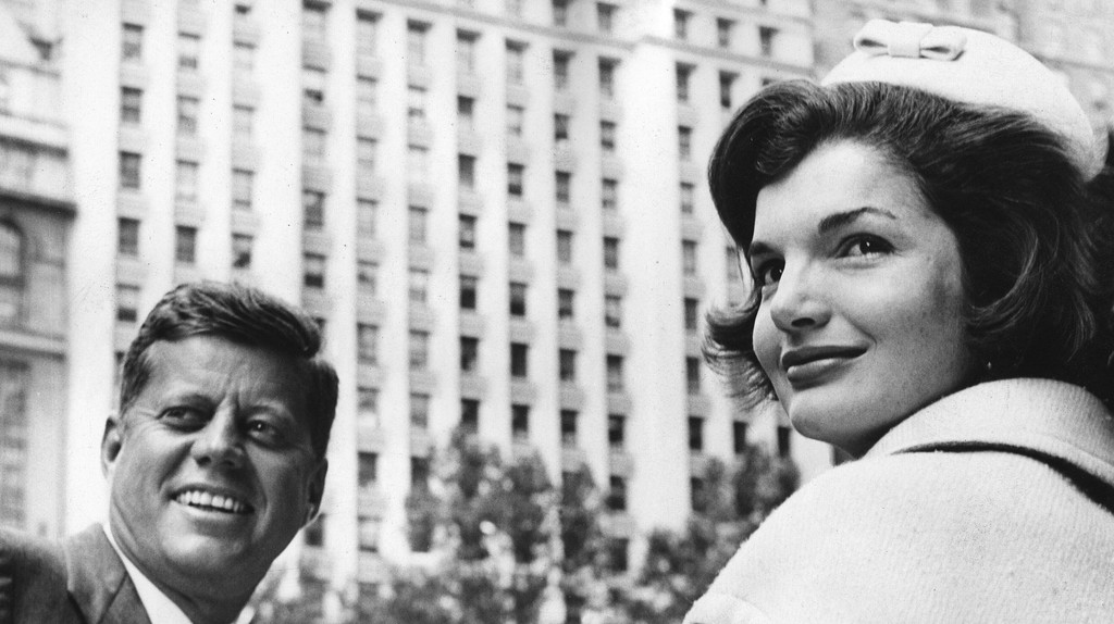 President John F Kennedy and First Lady Jackie Kennedy smile during a parade in New York in 1961