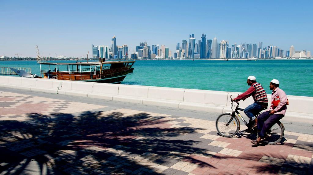 A cyclist with passenger pedals along the Corniche Promenade, Doha, Qatar