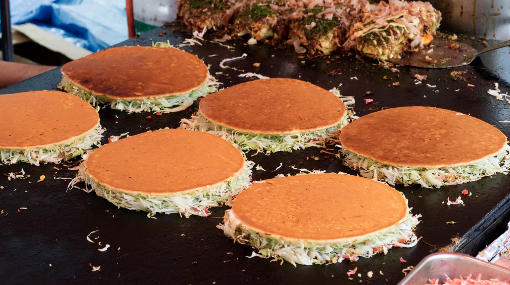 Baking savoury pancakes at a grill, Tokyo