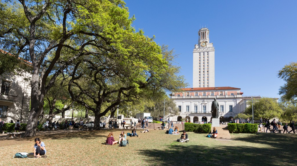 Students reading on the grass in spring sunshine, The University of Texas at Austin, Texas, USA.