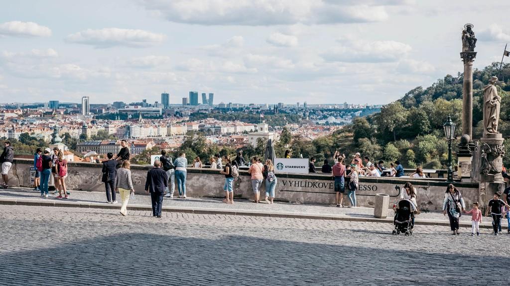 People walk on a viewing platform near Prague Castle