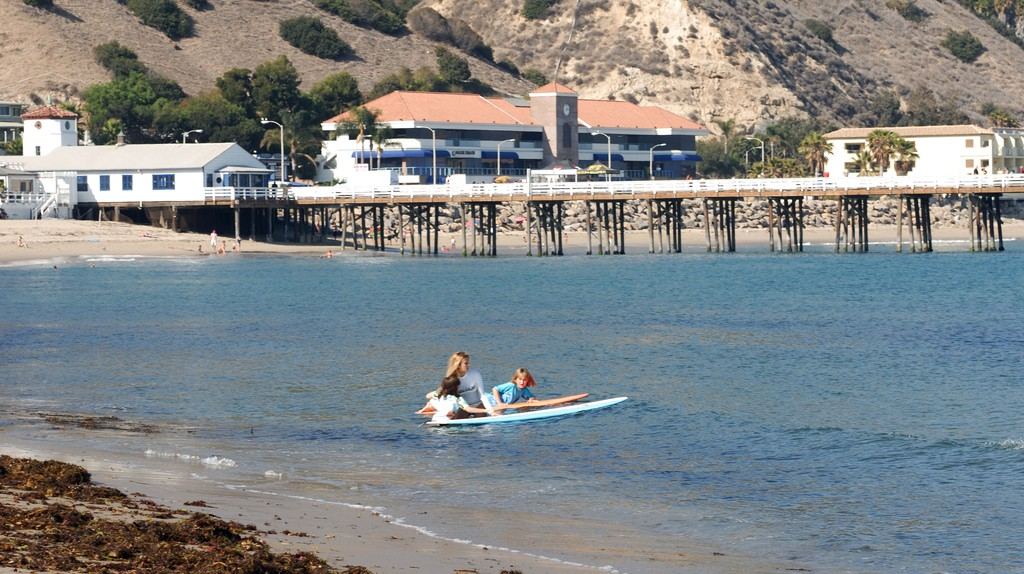 Mother and two daughters surfing in Malibu.