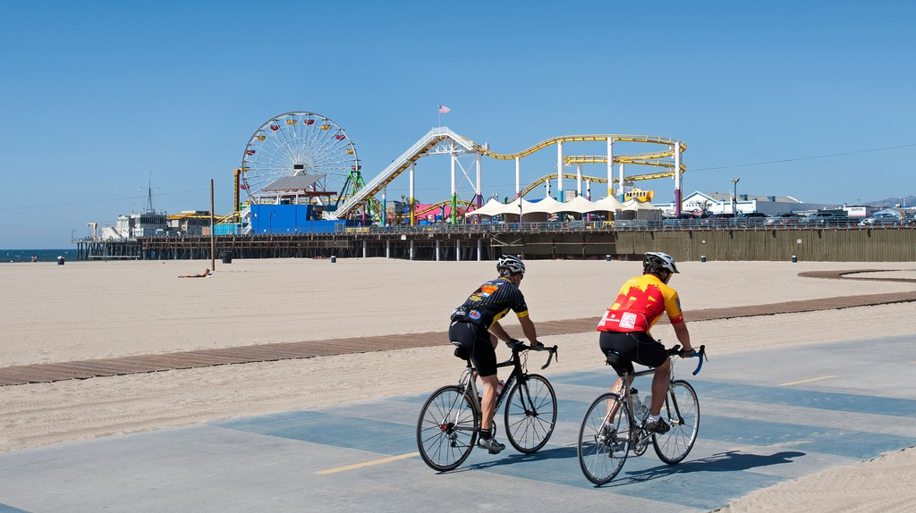 Two cyclists ride alongside Santa Monica Beach, California