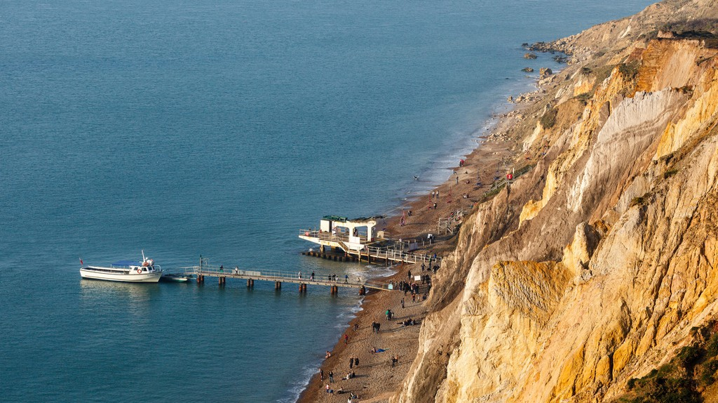 People take a stroll along Alum Bay, Isle of Wight, England