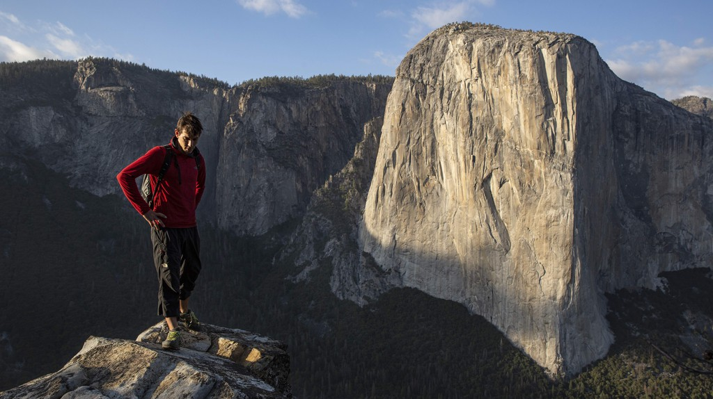 Alex Honnold stands withEl Capitan in the background
