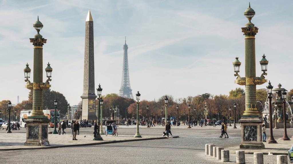 Groups of people take a stroll through Place de la Concorde, Paris