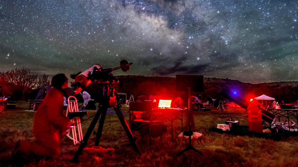 An observer at the Texas Star Party aims his telescope at a target in the Milky Way