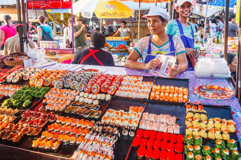 Ciudad de Phuket, Tailandia: Mujer que sirve sushi en el mercado de fin de semana.  El mercado está abierto todos los sábados y domingos.