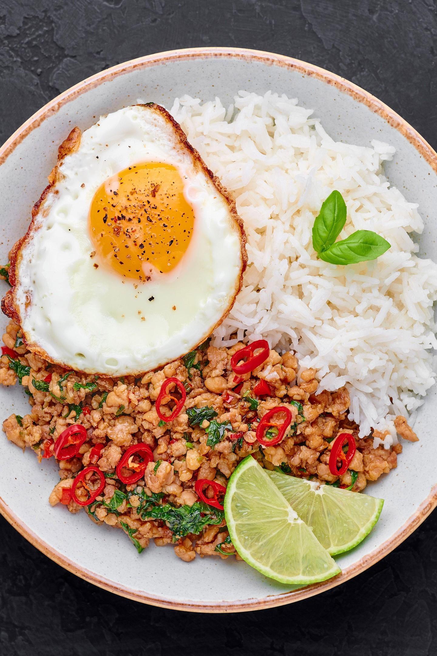 Pad Krapow Gai - Pollo a la albahaca tailandesa con arroz y huevo frito fondo de pizarra negra.  Pad Krapow es un plato de la cocina tailandesa con carne picada de pollo o cerdo,