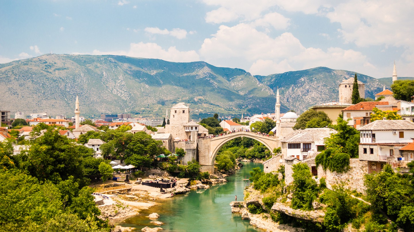 Beautiful view on Mostar city with old bridge, mosque and ancient buildings on Neretva river in Bosnia and Herzegovina   © Andrii Lutsyk/Shutterstock