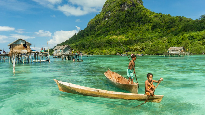 Sea Gypsy kids on a canoes in Bodgaya Island, Sabah Borneo, Malaysia