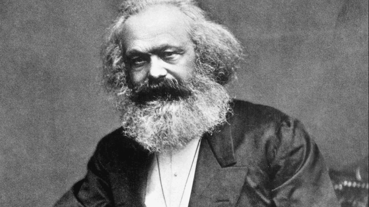 Photographic portrait of Karl Marx seated with a thumb in his lapel and his hand on his thigh, taken in the mid-1870s. | Photographer unknown.