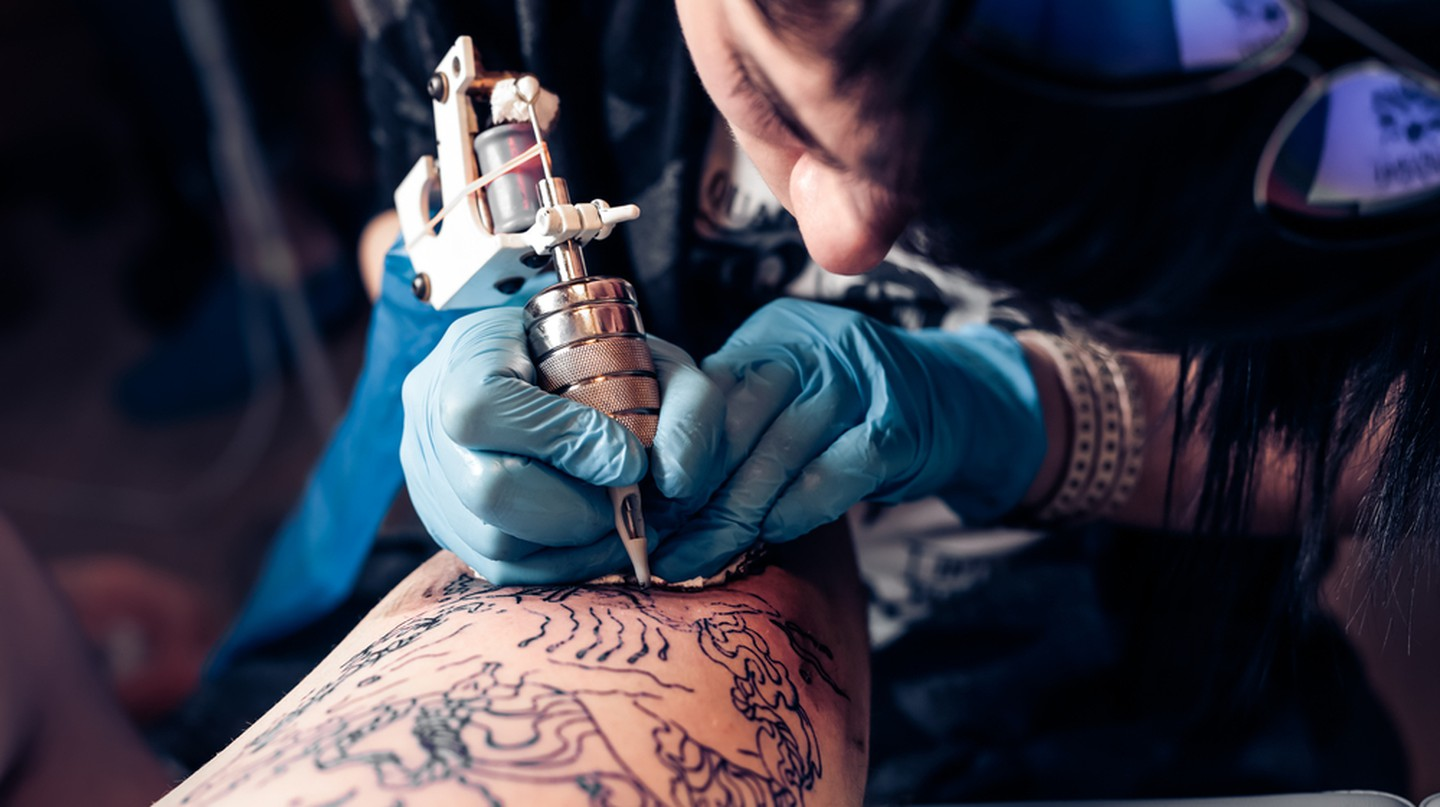 Tattoo Artist Outlining a Large Tattoo