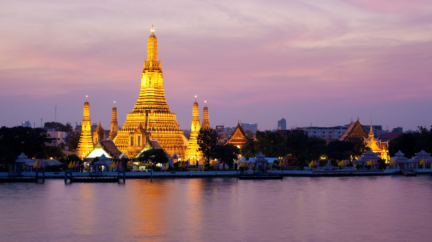 Wat Arun glows in the pink twilight by the Chao Phraya River, Bangkok