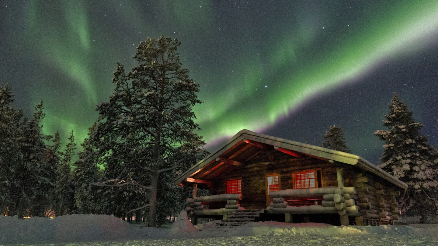 The northern lights above a wooden chalet |© Christ/ Flickr