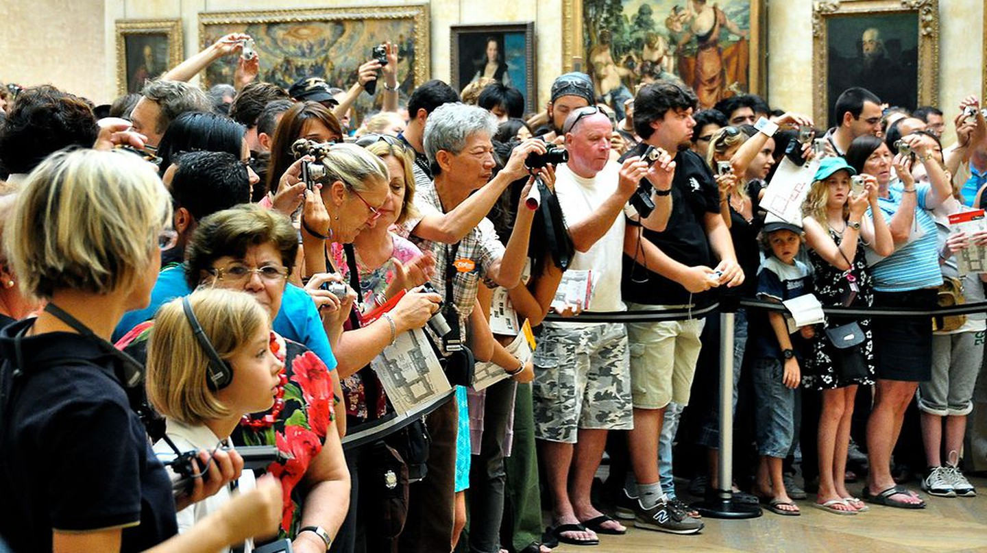 Crowd photographing the Mona Lisa │© tomarthur / Wikimedia Commons