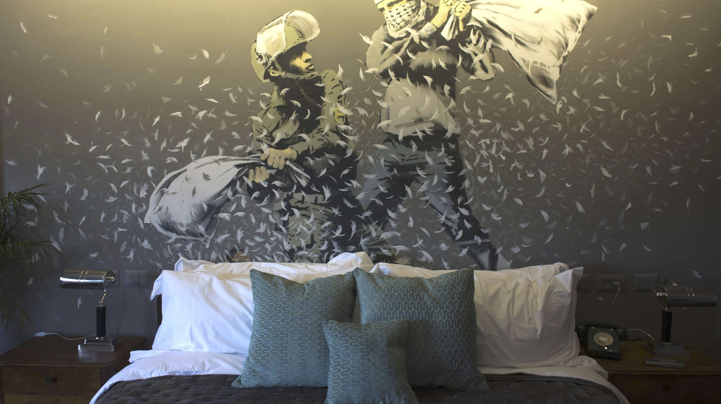 A wall painting by Banksy showing an Israeli border policeman and a Palestinian in a pillow fight