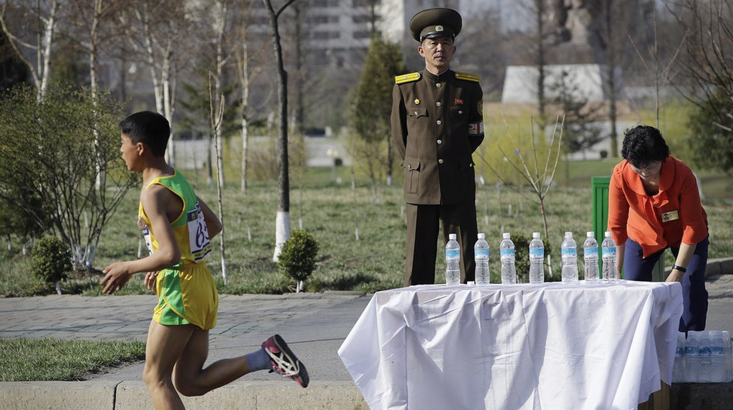 A soldier stands guard as runners pass during the 2017 Pyongyang Marathon | © AP/REX/Shutterstock