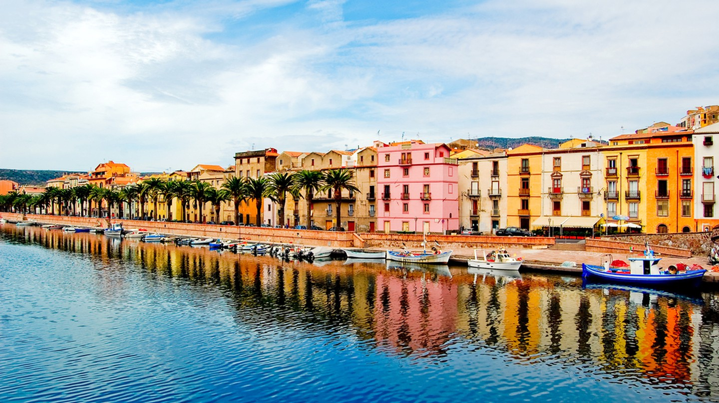 Houses and palm trees along the coast with reflection in bosa, sardegna | © Eugene Suslo / Shutterstock
