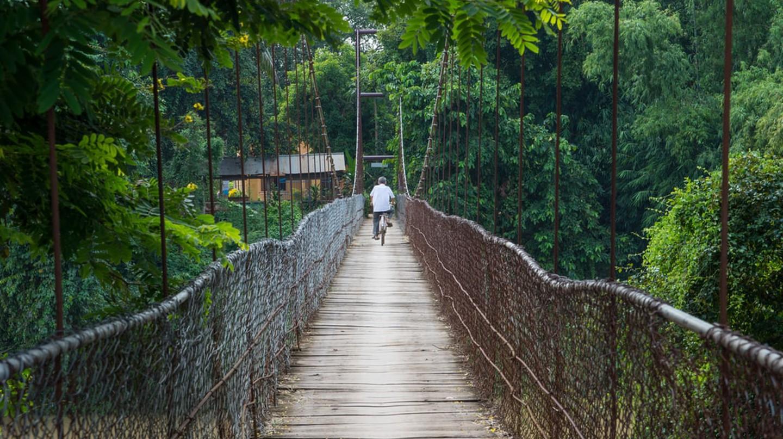 Man on bicycle crosses a bridge in Battambang, Cambodia | © RENATO SEIJI KAWASAKI / Shutterstock