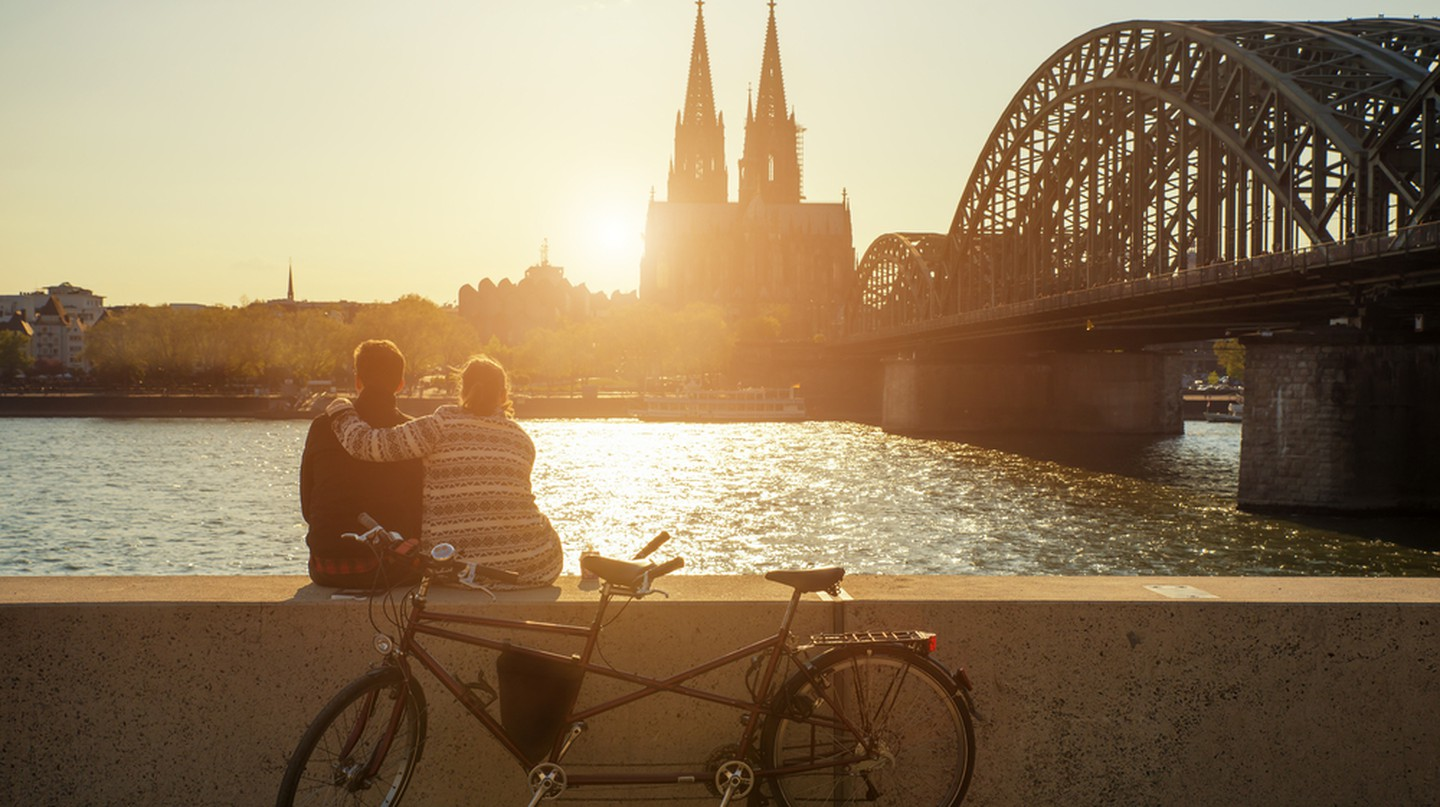 A young couple watches the sun set over Cologne Cathedral | © Prasit Rodphan / Shutterstock