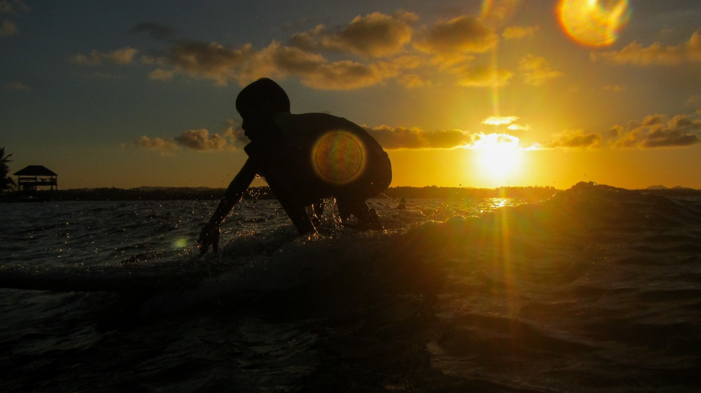 Surfing during golden hour in Siargao